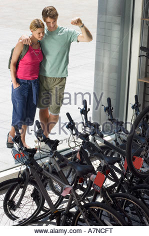 Young couple looking at new bikes in bicycle shop window display elevated view - Stock Photo