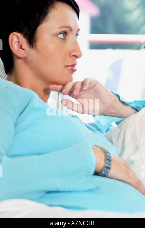 indoor flat room sittingroom woman young 25 30 brunette shirt blue jewelery bracelet sit couch hold stomach pregnancy - Stock Photo