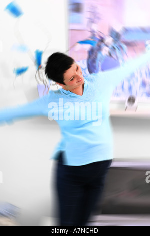 indoor flat room sittingroom woman young 25 30 brunette shirt blue stand dance stomach pregnancy pregnant move wall - Stock Photo