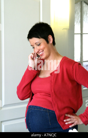 indoor flat room sittingroom woman young 25 30 brunette shirt cardigan red stand stomach pregnancy pregnant hold - Stock Photo
