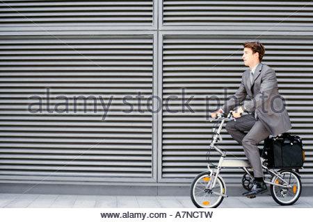 Businessman cycling on folding commuter bicycle on pavement profile - Stock Photo