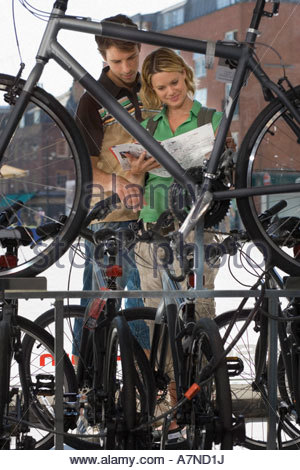 Young couple shopping for new bike in bicycle shop looking at brochure view through bike frame - Stock Photo