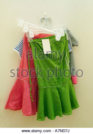 New green and pink skirts hanging on coathanger price tag attached close up - Stock Photo