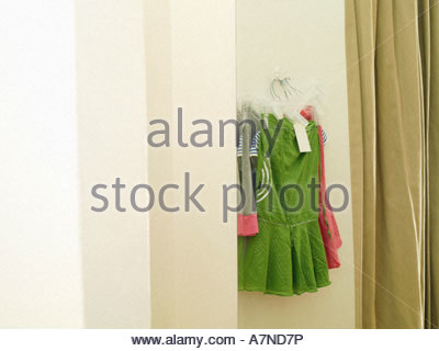 New green and pink skirts hanging on coathanger in clothes shop fitting room reflection in mirror - Stock Photo