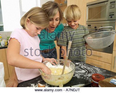 Mother and children 5 8 making cake mix in kitchen boy holding sieve girl dipping hand in bowl - Stock Photo