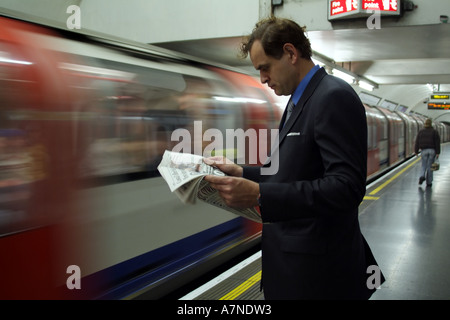 City gent reading newspaper on London Underground station with train approaching England United Kingdom - Stock Photo