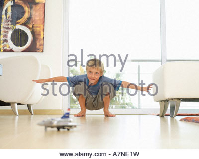 Boy 5 7 playing with toy plane on floor at home crouching arms outstretched surface level - Stock Photo