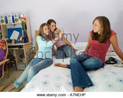 Three teenage girls 15 17 sitting on bed using mobile camera phone smiling - Stock Photo