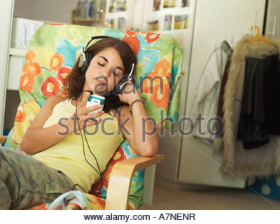 Teenage girl 15 17 sitting in armchair at home listening to MP3 player eyes closed tilt - Stock Photo