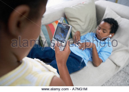 Two children 7 10 relaxing at home boy on sofa listening to MP3 player girl holding mobile phone - Stock Photo