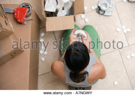 Woman sitting on floor packing box wrapping bowl in paper overhead view - Stock Photo
