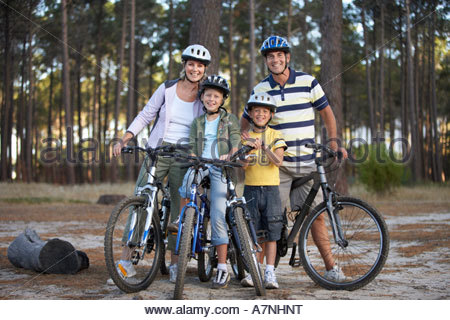 Two generation family standing beside bicycles in woodland clearing smiling portrait - Stock Photo