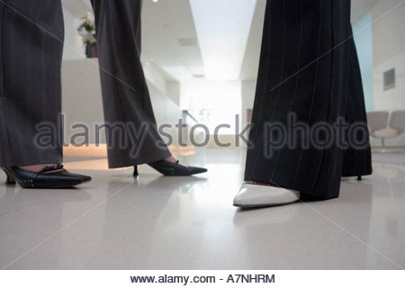 Two businesswomen wearing high heels and trousers talking in lobby side view low section surface level - Stock Photo