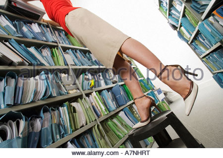 Woman wearing skirt and high heels searching for file in office archive standing on top of footstool in aisle side - Stock Photo