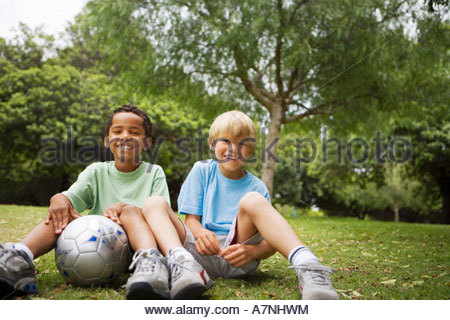 Two boys 6 8 sitting on grass with football in garden side by side smiling front view portrait - Stock Photo
