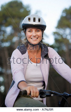 Woman wearing cycling helmet and pink hooded sports top sitting on bicycle smiling portrait - Stock Photo