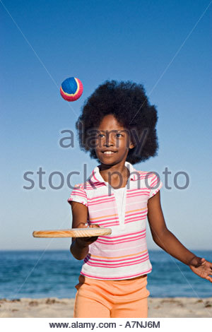 Girl 8 10 playing with bat and ball on sandy beach smiling front view portrait - Stock Photo