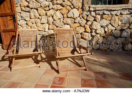 Two wooden deckchairs on tiled patio stone wall in background - Stock Photo
