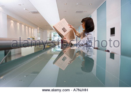 Businesswoman reading financial newspaper in lobby reflection on long glass table profile - Stock Photo