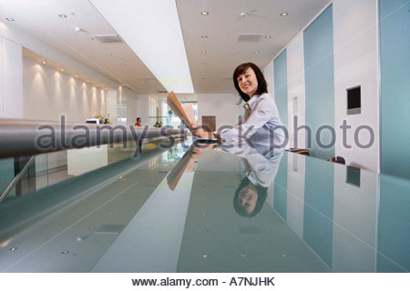 Businesswoman reading financial newspaper in lobby reflection on long glass table smiling side view portrait - Stock Photo