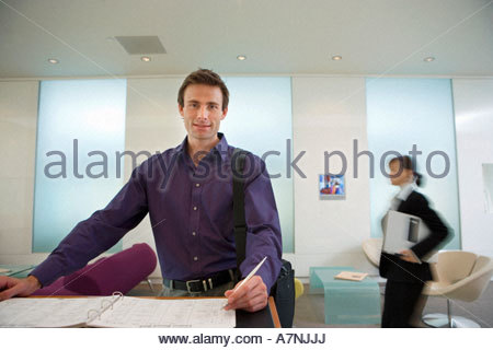 Businessman signing guestbook in reception area smiling portrait businesswoman in background focus on foreground - Stock Photo