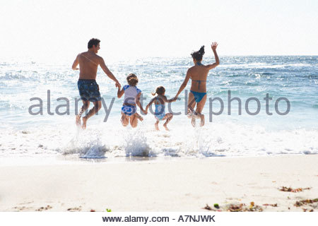 Two generation family wearing swimwear jumping above surf on sandy beach side by side holding hands rear view sunlight - Stock Photo