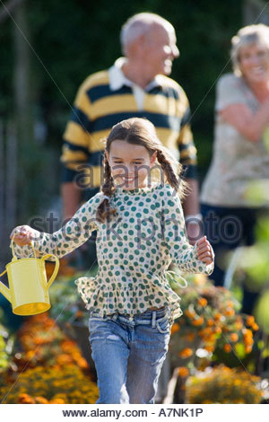 Girl 8 10 running in garden holding watering can smiling grandparents standing in background - Stock Photo