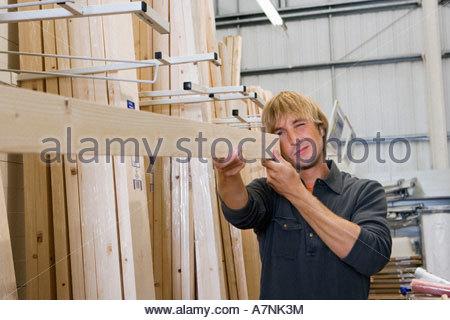 Man checking straightness of timber in DIY store - Stock Photo