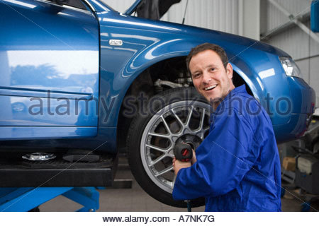 Male mechanic wearing blue overalls attaching wheel to car on hydraulic platform in auto repair shop smiling side - Stock Photo