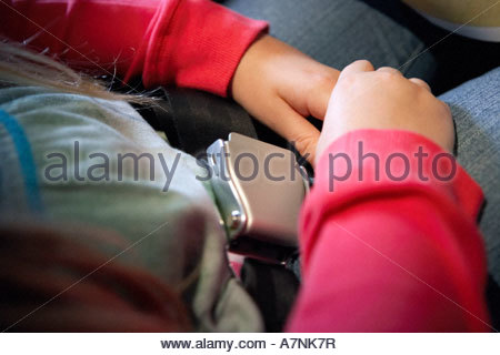 Woman sitting in airplane wearing seat belt side view close up - Stock Photo