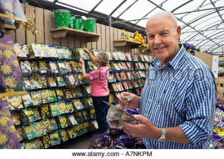 Senior couple shopping in garden centre man holding flower bulbs smiling side view portrait - Stock Photo