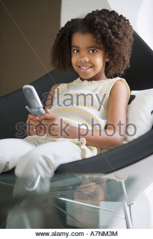 Girl 5 7 text messaging on mobile phone sitting in chair smiling portrait - Stock Photo