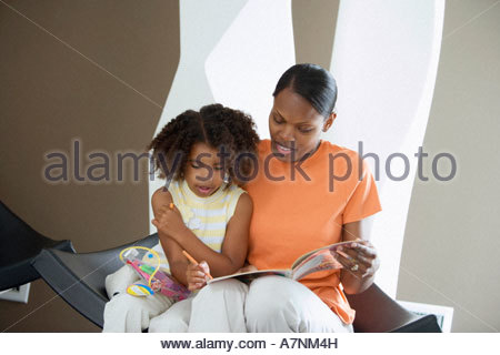 Mother and daughter 5 7 sitting at home girl colouring picture in book with felt tip pen - Stock Photo