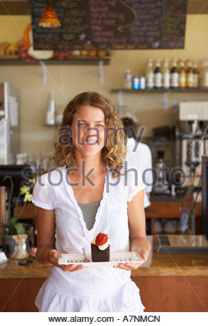 Waitress working behind counter in cafe focus on woman carrying dessert smiling portrait - Stock Photo