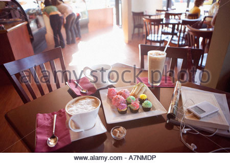 Iced coffee latte black coffee and cakes on serving dish beside MP3 player and publications on cafe table elevated - Stock Photo