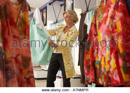 Mature blonde woman shopping in clothes shop choosing between two different coloured tops side view - Stock Photo