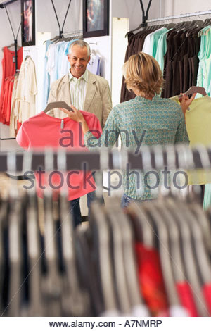 Mature couple shopping in clothes shop woman showing two different coloured tops to husband man smiling focus on - Stock Photo