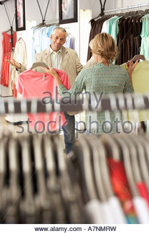 Mature couple shopping in clothes shop woman showing two different coloured tops to husband man shrugging shoulders - Stock Photo