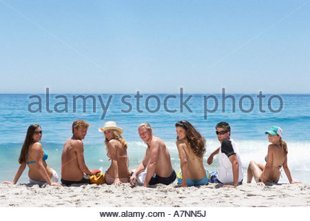 Teenagers 16 18 sitting on beach looking over shoulder side by side rear view portrait - Stock Photo