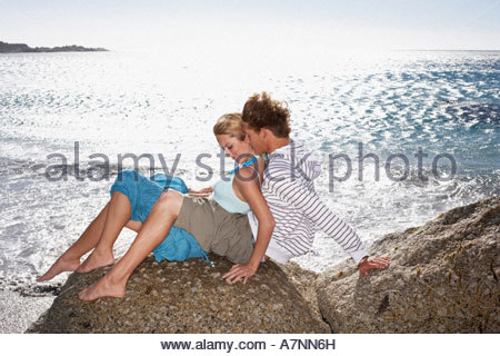 Teenage couple 17 19 sitting on rocky beach in bright sunlight girl in boy s lap smiling - Stock Photo