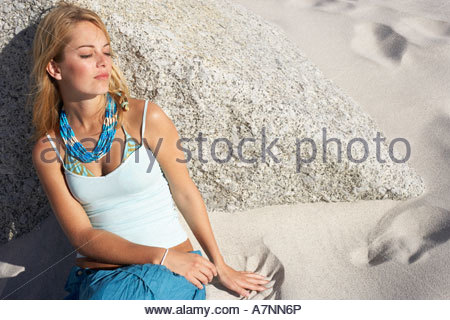 Blonde teenage girl 17 19 relaxing on beach leaning against rock eyes closed elevated view - Stock Photo