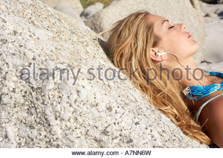Blonde teenage girl 17 19 relaxing on beach leaning against rock eyes closed side view - Stock Photo