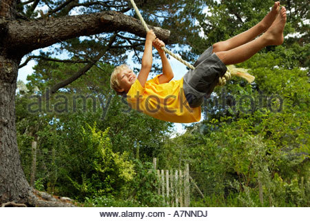 Boy 7 9 swinging on rope swing hanging from tree in garden smiling side view - Stock Photo