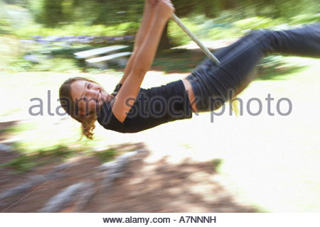 Girl 9 11 swinging on rope in garden smiling side view blurred motion - Stock Photo