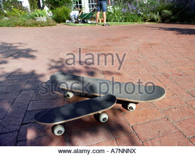 Two black skateboards on brick driveway father and son on lawn in background - Stock Photo