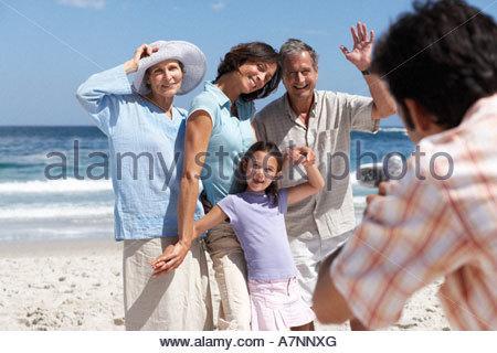 Man photographing three generation family on sandy beach portrait focus on background - Stock Photo