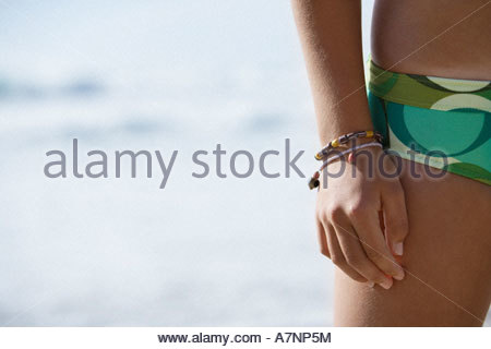 Young woman standing on beach wearing green bikini mid section close up front view - Stock Photo