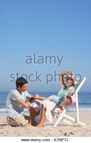 Young family sitting on sandy beach daughter 2 3 lying in mother s lap portrait - Stock Photo