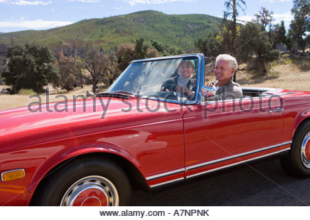 Mature couple driving in red convertible car along country road smiling side view - Stock Photo