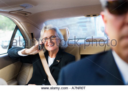 Senior businesswoman using mobile phone in back seat of chauffeur driven car smiling front view - Stock Photo